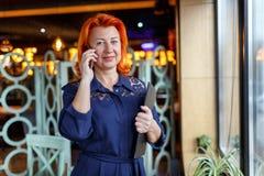 Une femme avec un léger sourire parle au téléphone avec un comprimé dans sa main images libres de droits