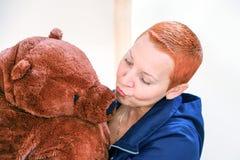 Une femme avec un ours de nounours Femme embrassant l'ours de nounours d'isolement sur le fond clair image stock