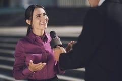 Une femme avec un sourire sur son visage répond à la question Un homme tient un microphone écoutant une réponse Image libre de droits
