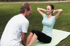 Une femme bascule la presse sur la nature Elle s'assied sur une couverture pour le yoga Un homme l'aide et tient ses jambes Photo libre de droits