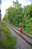 Une femme birmanne supporte une charge lourde des cannes coupées sur sa tête le long des voies du chemin de fer birman, entre Yan photo stock
