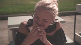 Une femme blonde affamée mangeant un hamburger sur la rue La jeune femme mangent ardemment un hamburger, se tenant dans leurs mai clips vidéos