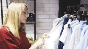 Une femme blonde choisissant des vêtements dans une salle d'exposition de boutique images stock