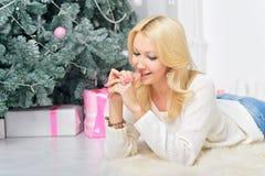 Une femme blonde déroulant la nouvelle année coloré emballée se présente Photo stock