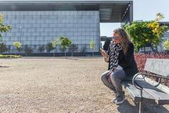 Une femme blonde mûre vérifie son téléphone portable tout en se reposant en parc images stock