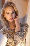 Une femme blonde magnifique s'asseyant avec un chemisier et des bijoux de dentelle photo stock