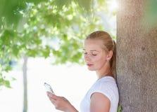 Une femme blonde surfant l'Internet avec son smartphone Photographie stock libre de droits