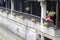 Une femme chinoise dans la robe rouge en ville antique de Feng Jing Image stock