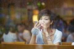 Une femme chinoise parlant au smartphone dans le café Photo libre de droits