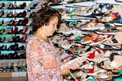 Une femme choisit les chaussures confortables dans un boutique_ à la mode image stock