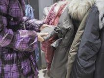Une femme choisit une veste dans le magasin photo stock
