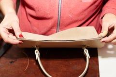 Une femme colle deux parts en cuir ensemble, utilisé dans la production des chaussures, des sacs à main photo libre de droits