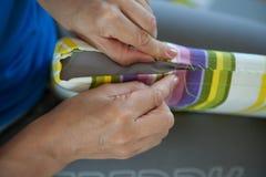 Une femme coud un tissu lumineux avec une aiguille Couture manuelle pointeau Image libre de droits