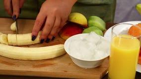 Une femme coupe une banane afin de la mettre dans un mélangeur Tiré avec le chariot banque de vidéos