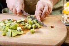 Une femme coupe en petits morceaux d'un couteau de kiwi sur un conseil en bois Images libres de droits