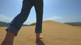 Une femme court le long du sable dans le désert Une fille court nu-pieds sur une dune de sable dans le sable banque de vidéos