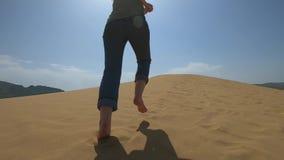 Une femme court le long du sable dans le désert Une fille court nu-pieds sur une dune de sable dans le sable clips vidéos