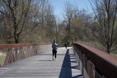 Une femme court plus de Wolf River Bridge Photos stock