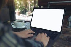 Une femme d'affaires à l'aide de l'ordinateur portable avec l'écran de bureau blanc vide avec la tasse de café sur la table en bo Photographie stock