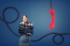Une femme d'affaires attrapée et liée par de grandes cordes de téléphone noires près d'un récepteur rouge géant de téléphone image stock