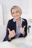 Une femme d'affaires de sourire plus âgée dans le bureau avec des pouces  Photographie stock