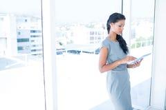 Une femme d'affaires focalisée à l'aide du comprimé numérique Images stock