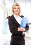 Une femme d'affaires heureuse avec le dépliant bleu Images stock