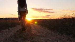 Une femme d'affaires marche le long d'une route de campagne avec un comprim? dans sa main, le miertsaet du soleil entre les jambe banque de vidéos