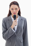 Une femme d'affaires sérieuse retenant un microphone Photos stock