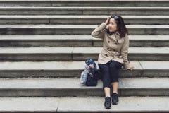 Une femme d'affaires s'asseyant à l'échelle concrète en parc Photo libre de droits