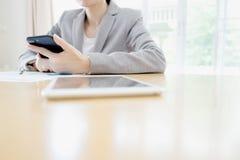 Une femme d'affaires tenant le smartphone au bureau Image stock