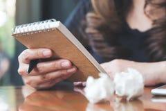 Une femme d'affaires travaillant et tenant un carnet vide blanc avec vissés les papiers sur la table image stock