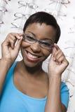 Une femme d'Afro-américain essayant sur des verres images stock