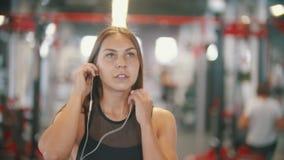 Une femme d'athlète marchant dans le gymnase et mettant sur des écouteurs clips vidéos