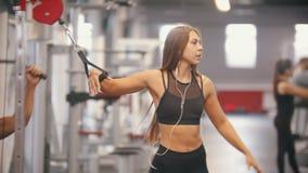 Une femme d'athlète marchant dans le gymnase et mettant sur des écouteurs - obtenez ses mains dans les poignées et commencez la f banque de vidéos