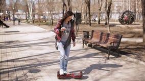 Une femme d'une cinquantaine d'années apprend à monter un scooter électronique banque de vidéos