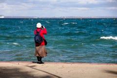 Une femme d'une cinquantaine d'années photographie le paysage marin image libre de droits