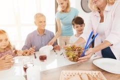 Une femme d'une cinquantaine d'années sert une salade pour sa famille sur la table, qui vont dîner Photos stock