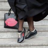 Une femme dans des espadrilles avec un sac et une jupe noire Photographie stock