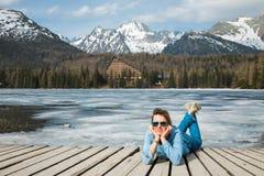Une femme dans des jeans se trouvant par le lac congelé Strbske Pleso de montagnes photographie stock