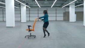 Une femme dans des vêtements de bureau roule heureusement une chaise de roulement le long du hall clips vidéos