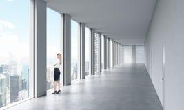 Une femme dans des vêtements formels regarde la fenêtre Intérieur propre lumineux moderne vide d'un bureau de l'espace ouvert WI  Photos stock
