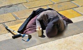 Une femme dans des vêtements noirs avec une béquille priant pour l'aumône se trouvant sur les escaliers Photos libres de droits