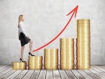 Une femme dans des vêtements formels va consommation les escaliers qui sont faits de pièces de monnaie d'or La flèche rouge est d Photographie stock