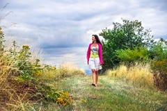 Une femme dans une jupe blanche marche le long d'un chemin de champ sous un summe Image libre de droits