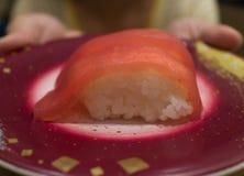 Une femme dans le T-shirt jaune s'est tenue apportante un plat des sushi japonais frais Makuro d'Akami Nigiri photo stock