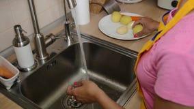 Une femme dans les légumes de lavage de cuisine dans banque de vidéos