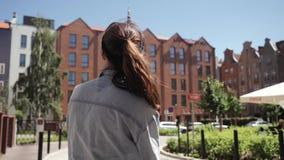 Une femme dans les promenades de touristes de lunettes de soleil voyageant par les rues européennes, regards autour banque de vidéos