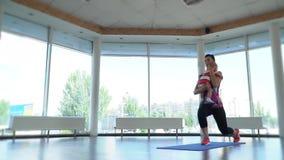 Une femme dans les vêtements de sport est engagée dans les postures accroupies sur un tapis de yoga tenant son bébé à son sein, m banque de vidéos