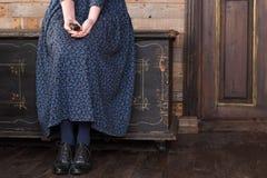Une femme dans une longue robe bleue s'assied sur un coffre noir et tient une vieille serrure avec une clé Photographie stock
